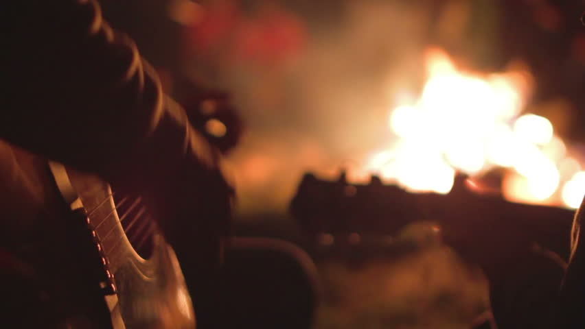 Playing the guitar at campfire.