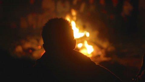 Teenage boy at summer camp looking at camp fire.