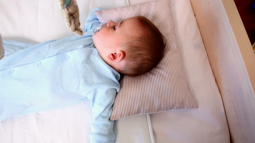 Baby boy sleeping in crib at home in bedroom