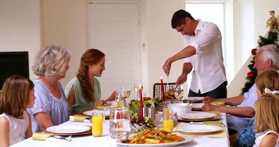 Father Carving The Turkey At Head Of Table Christmas Home In