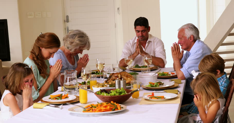Extended Family Praying Together Before Dinner At Home In The Dining Room
