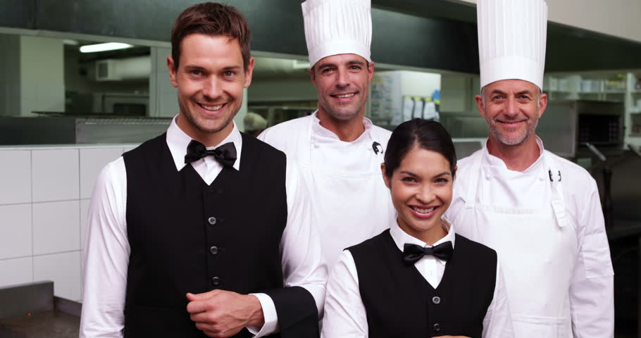 Restaurant Kitchen Staff happy restaurant staff smiling at camera in a commercial kitchen
