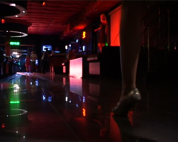 Close-up of lady steps over floor in night club