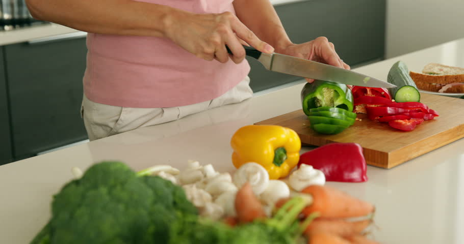 Woman slicing green pepper and smiling at camera at home in the kitchen #5943908