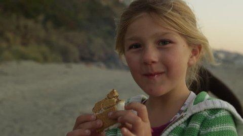 Young girl eats smores on the beach - 4K