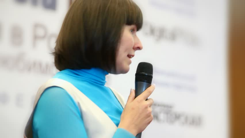close-up portrait of woman speaking through a microphone in conference hall