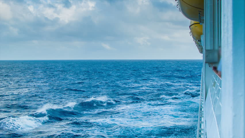 Onboard a Cruise Ship Sailing the Open Ocean, seen with Life Boats Hanging on the Side of the Vessel with a Sea Scape Horizon and Clouds.