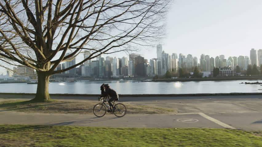 Dolly shot of cyclist riding along seawall at sunset with Vancouver skyline in background.