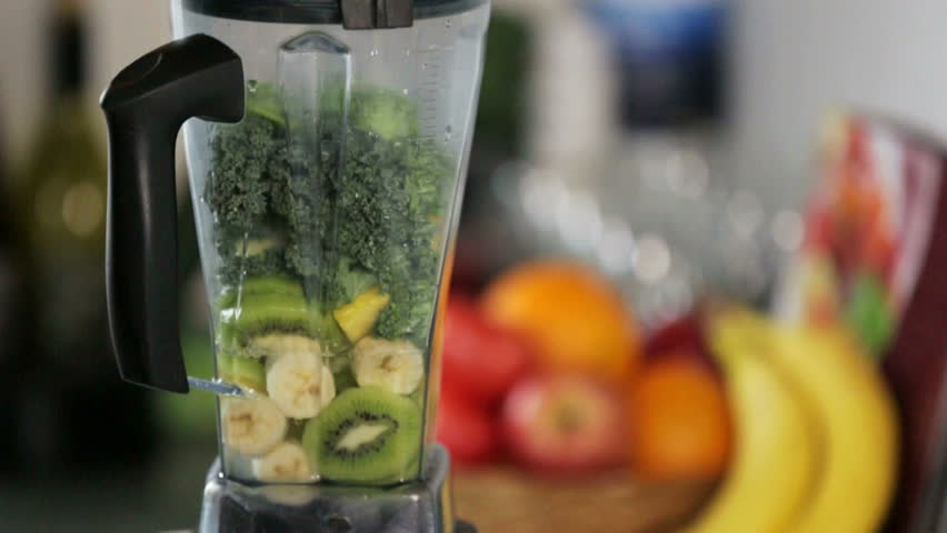 Fruits and Vegetables are blended up into a healthy green smoothie in slow motion