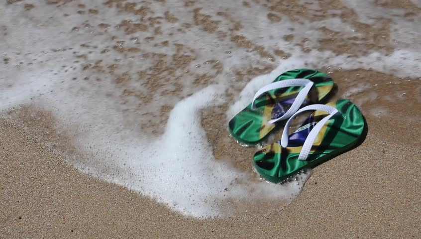 Brazilian Flipflops decorated with Brazil flag, on the beach near the sea