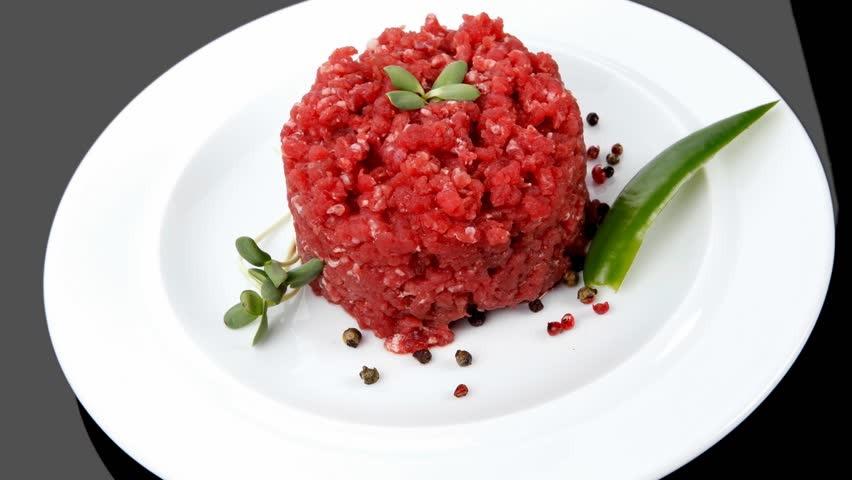 very big raw hamburger cutlet with sprouts and chilli pepper plate over black background 1920x1080 intro motion slow hidef hd