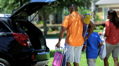 African American family putting chairs bags into back hatchback car ready for outing - Young African American Family Car Outing