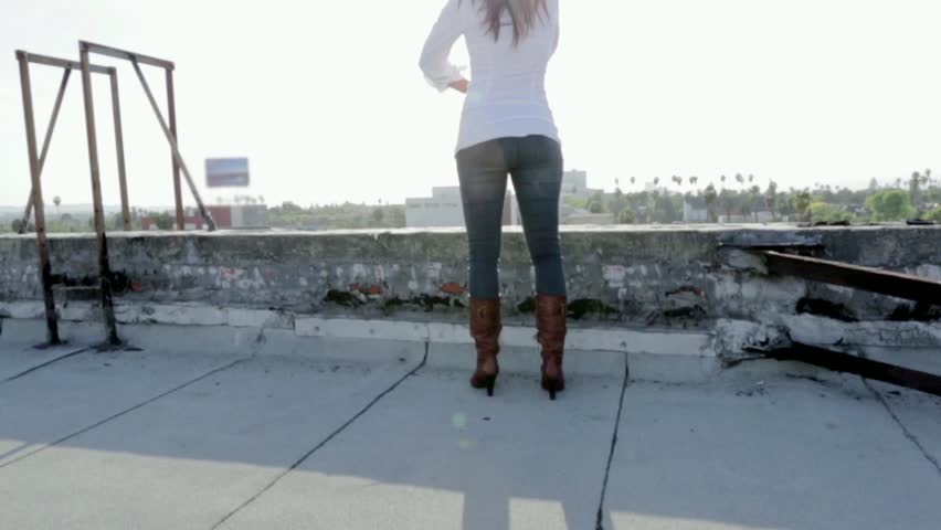 Woman on a rooftop with her arms wide open looking at view  #6026162