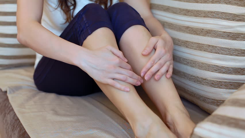 girl rubs tired legs sitting on the couch