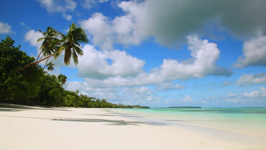 Time-lapse of white sand tropical beach with turquoise water, coconut trees swaying in the wind and clouds passing by. | Shutterstock HD Video #6039092