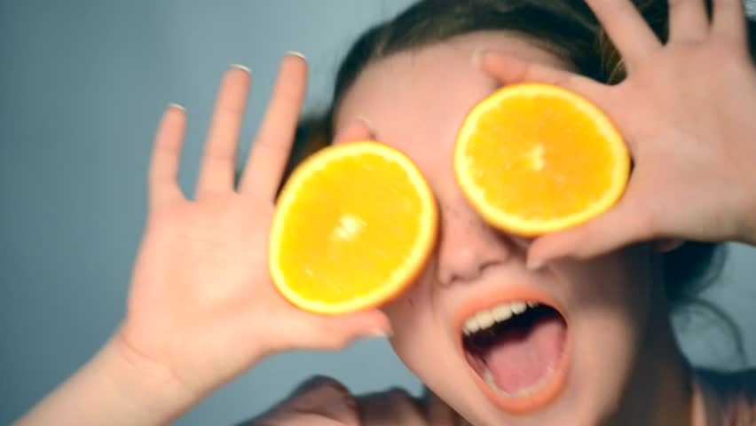 Beauty Model Girl takes Juicy Oranges. Beautiful Joyful teen girl with freckles, funny red hairstyle and yellow makeup. Professional make up. Orange Slices in fast motion.