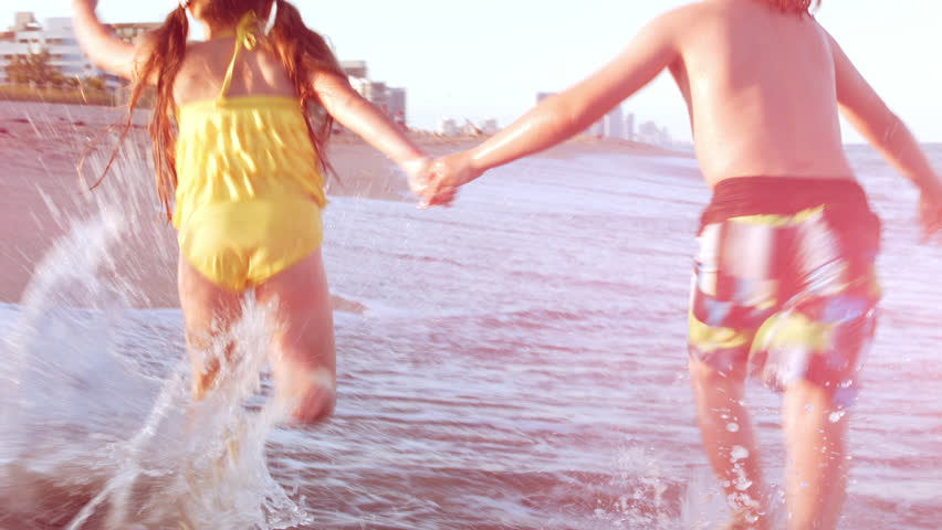 Little Kids Hold Hands And Run As Fast As They Can (Away From Camera) Down Beach, Beautiful Lens Flare    Shutterstock HD Video #6069209