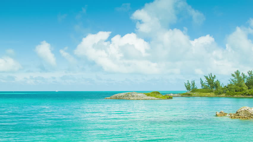 An Exotic Island Setting in Tropical Waters, with Turquoise Colored Water, Lush Green Foliage and a Blue Sky with White Clouds on a Sunny Day in Bermuda.