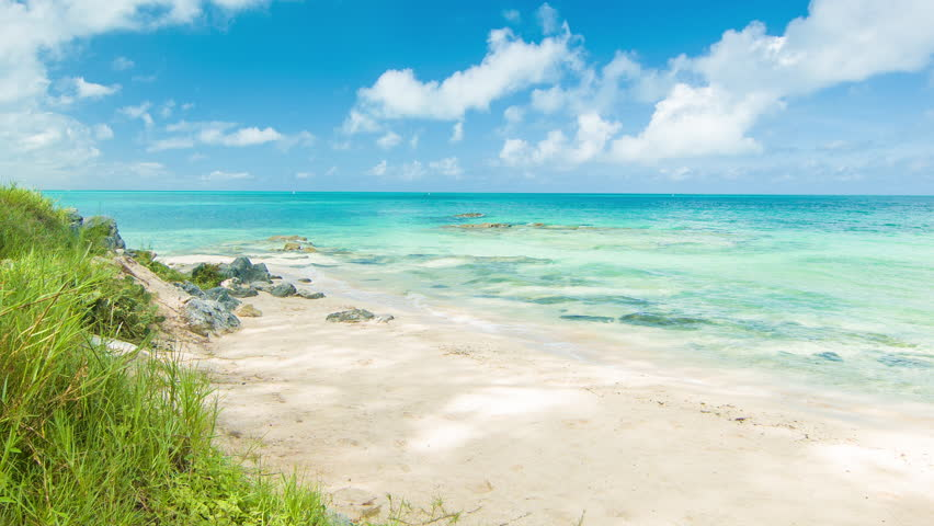 A Picture Perfect Private Beach in Bermuda on a Sunny Day featuring Tropical Water, Green Grass, Golden Sand Beach and White Clouds in a Blue Sky.