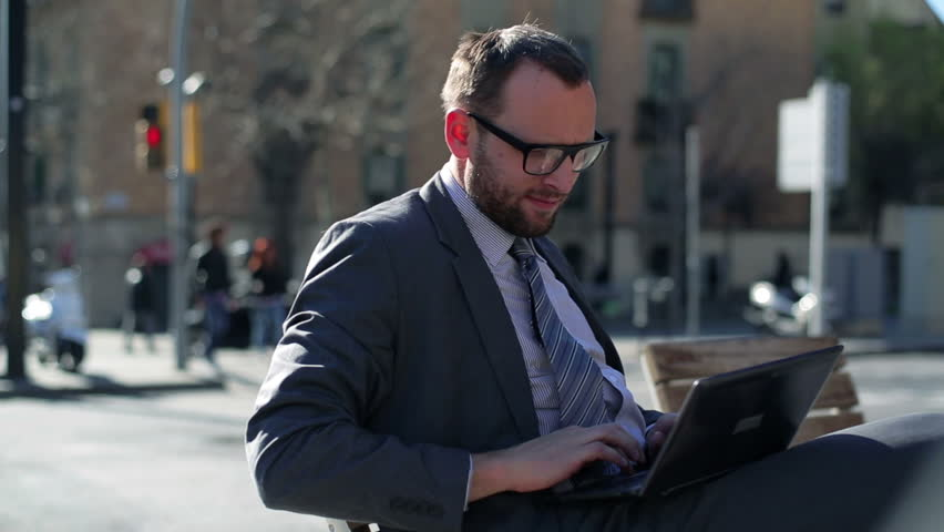 Businessman working on laptop and sitting on street bench, steadycam shot.