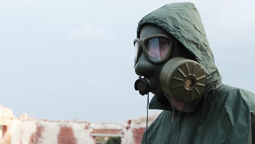 The man with gas mask and decontamination suit,protective suit,looking around on abandoned building,abstract shot apocalypse,scene polluted environment,cloudy background,cloudy sky,close up face,24fps - HD stock video clip