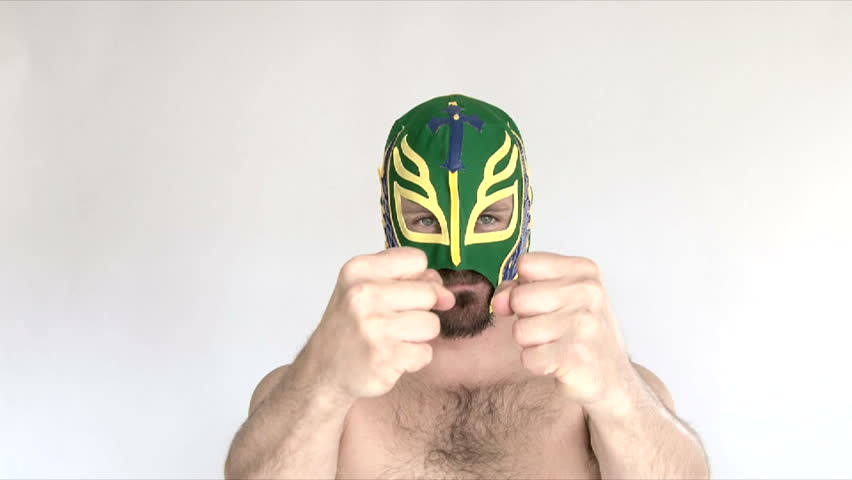 Model released man in studio wearing green lucha libre mask challenges and threatens camera.