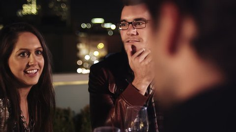 Two couples sitting at a table on a rooftop bar at night laugh and drink together
