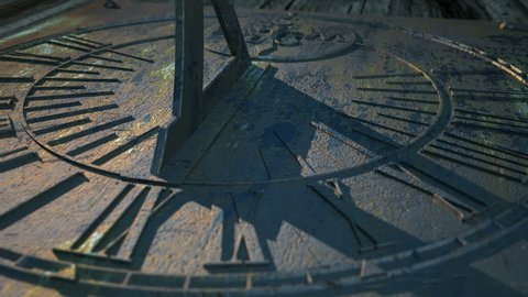 A macro panning closeup of a sundial in a twelve hour time-lapse going from morning until night