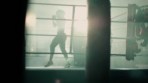 Female Boxer enters the ring jogging and prepares for the fight