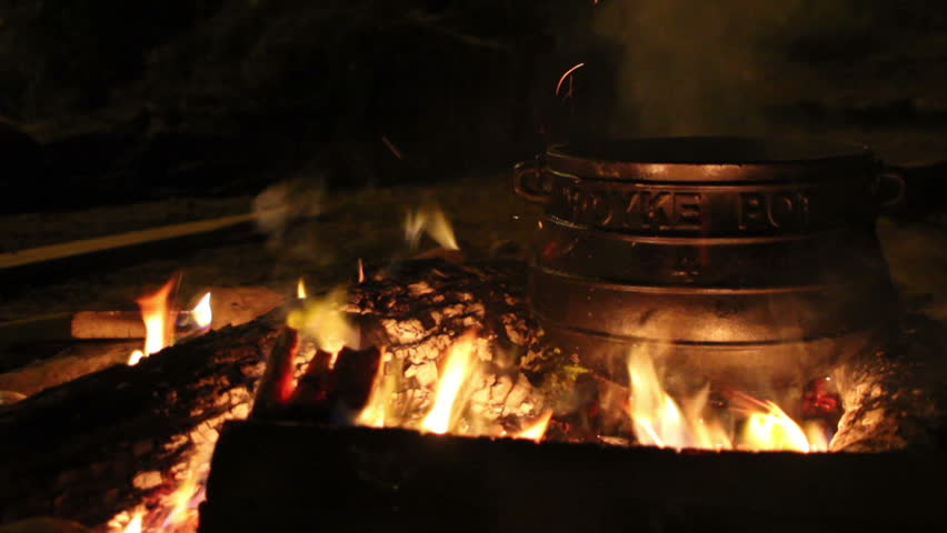 Cooking in a big black pot on open fire.