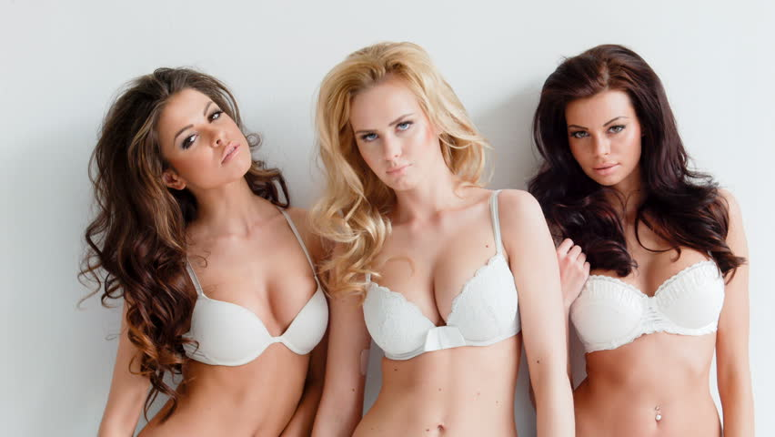 cf47e98115 Three sensual beautiful beguiling young women wearing white lingerie  looking seductively at the camera as they pose together in a group
