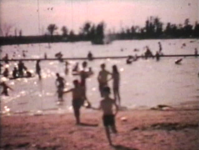 A shot of a crowded beach with tons of kids playing in the water and then a little boy runs towards the camera. (Vintage 8mm film)