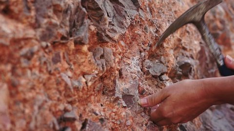 Close up shot of a geologist taking a mineral rock sample of an iron ore stained deposit.