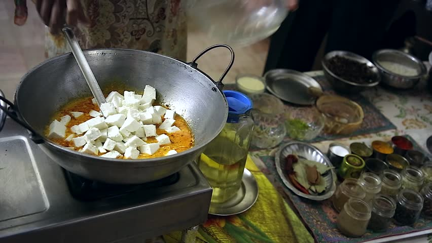 Local cuisine & technique are demonstrated by Indian woman in New Delhi, India. Here a paneer dish is prepared. Paneer is cottage or farmer's cheese that makes up a large portion of vegetarian meals.