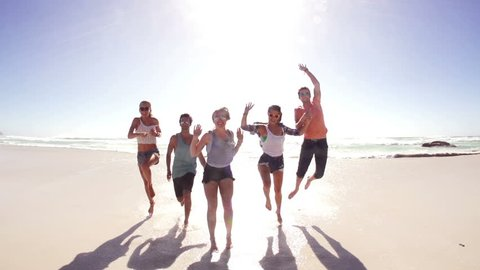 Friends running and jumping to camera on beach in slow motion