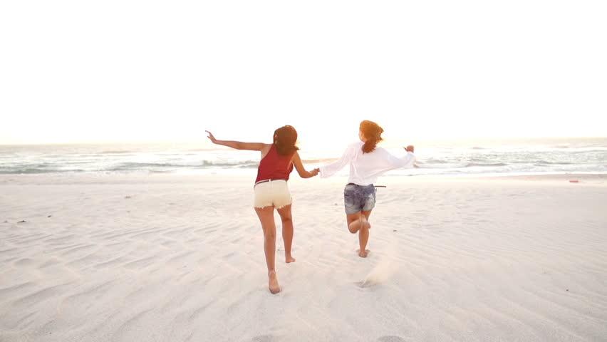 Best Friends Jumping Down The Beach