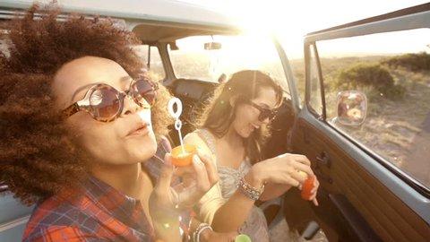 Friends blowing bubbles on road trip in slow motion