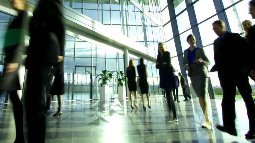 Time lapse of diverse business group in a large modern corporate building