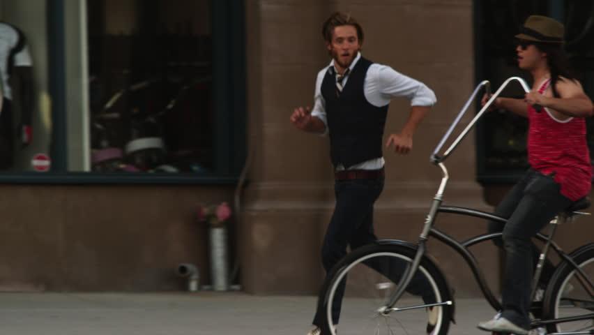 Medium Shot Two young men riding bicycle on street