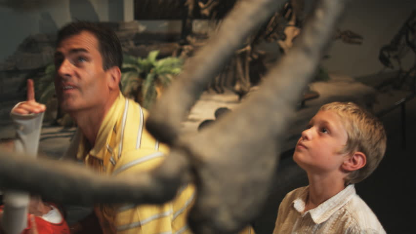 Medium Shot Father with daughter (8-9) and son (10-11) looking at dinosaurs skeleton in natural history museum