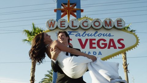 MONTAGE Medium Shot LA Newly wed couple dancing and kissing by Las Vegas welcome sign / Las Vegas,Nevada,USA