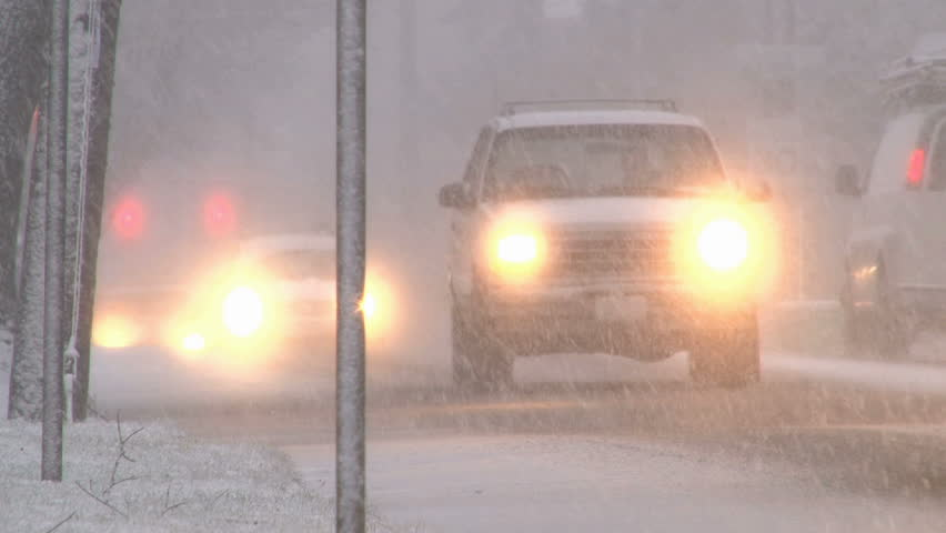 Blizzard conditions with vehicles driving on snow filled roads in Portland,