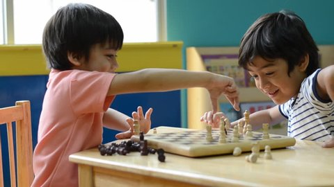 Little  asian mix arabic sibling boy playing chess  in a classroom- the last chess out become winner