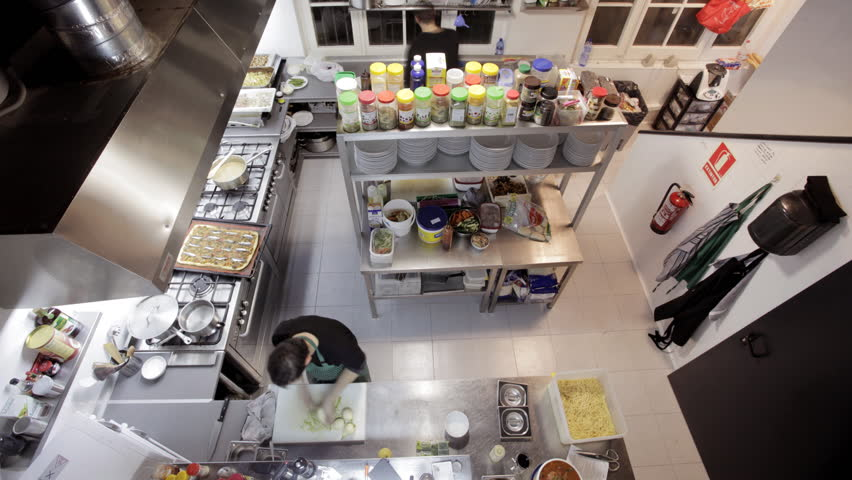 Restaurant Kitchen Video timelapse shot looking down on two chefs preparing food in a busy