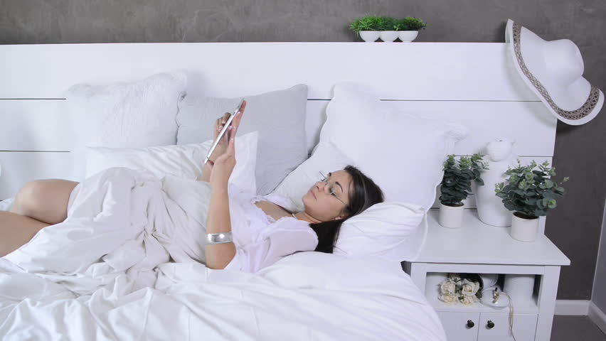 Beautiful Modern Brunette Woman Using Tablet Computer In Luxury White  Bedroom   HD Stock Video Clip