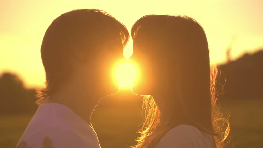 Romantic young couple silhouette is kissing on a sunset with sun shining bright behind them on a horizon. Slow motion filmed at 250 fps. First kiss of young love.