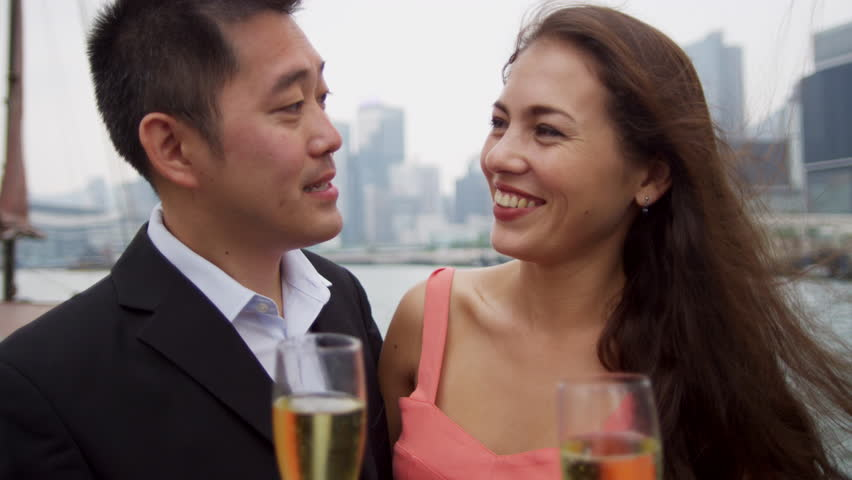 Close up young heterosexual Asian Western couple enjoying glass of wine  cityscape view Hong Kong Island