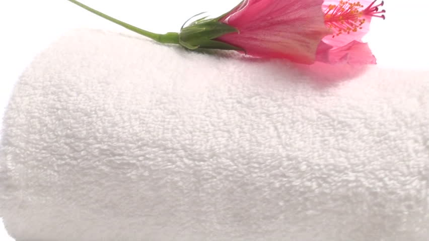 Zoom out on Spa towel topped with hibiscus flower isolated on white V3
