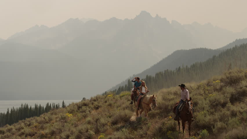 Wide shot of friends horseback riding near lake / Redfish Lake, Idaho, United States
