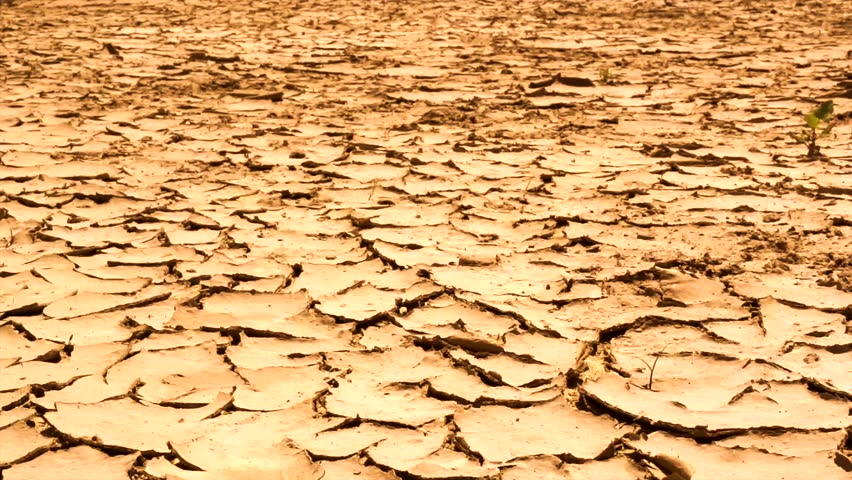 Cracked dry earth. Dried and cracked land. Global warming concept. Slow motion video footage 1080. High speed camera shot